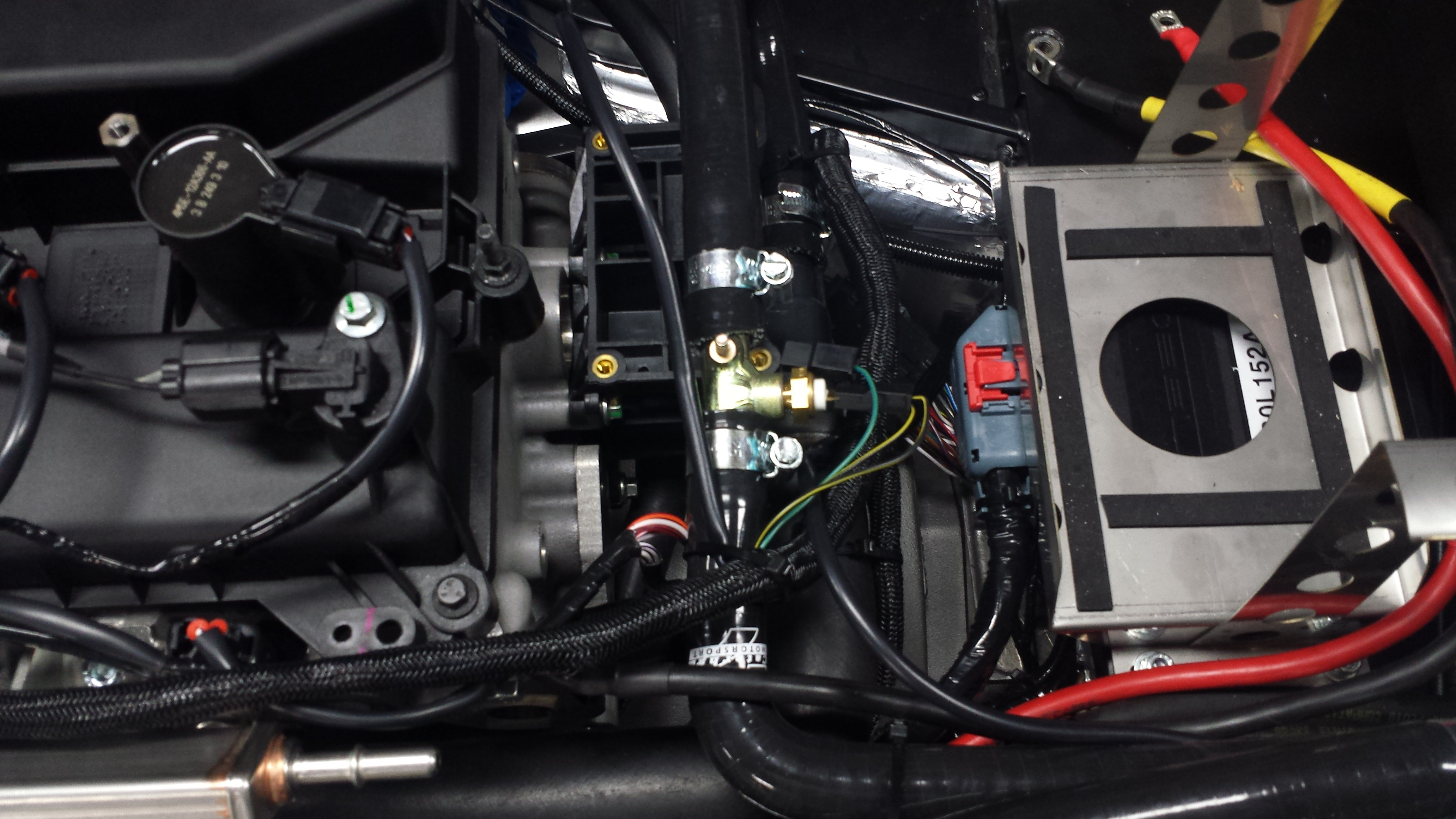 Wiring loom route on top of engine